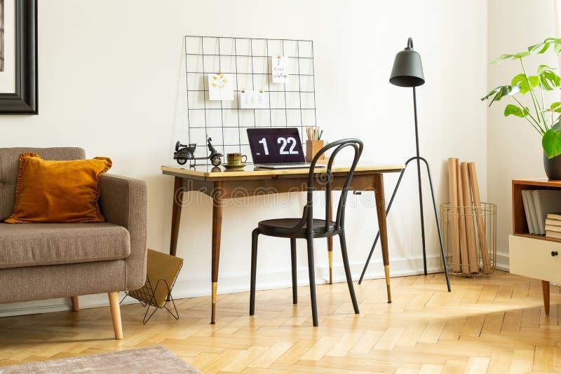 Foto real de uma mesa simples com um portátil, cadeira, organizador da parede em seguida um sofá em um interior do escritório dom imagens de stock royalty free