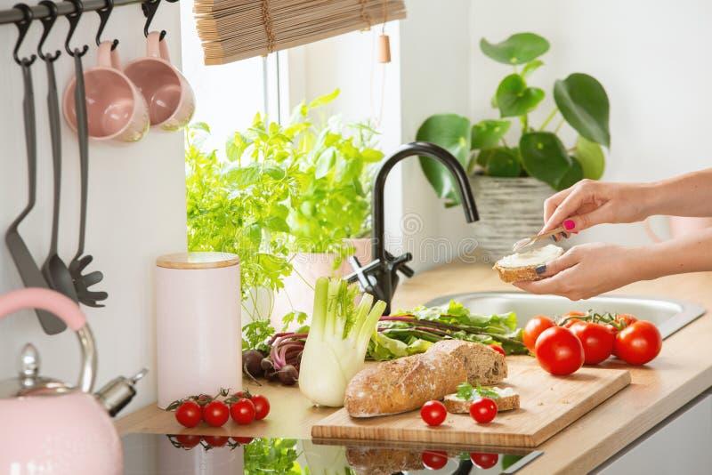 Foto real de uma mulher que faz sanduíches para o café da manhã em um brigh foto de stock