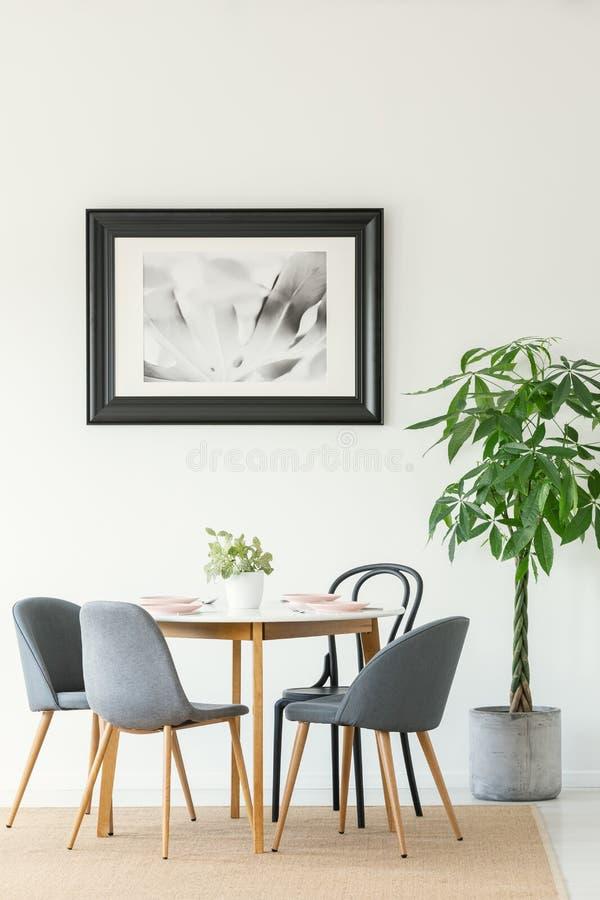 Foto real de un interior del comedor con una tabla, las sillas, el árbol y la pintura en un marco negro imagen de archivo libre de regalías