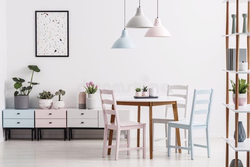 Foto real de un interior en colores pastel del comedor con una tabla, sillas fotografía de archivo libre de regalías