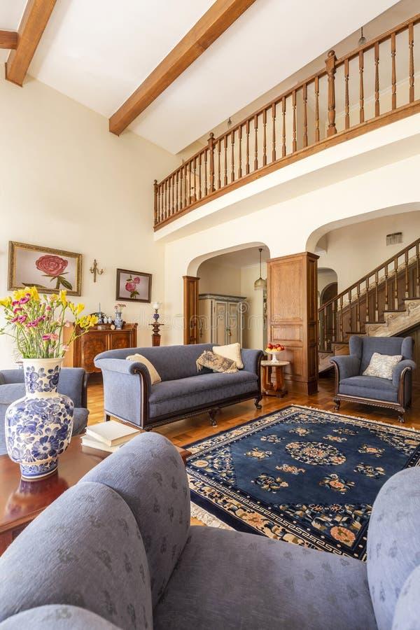 Foto real de un interior de la sala de estar con el sofá azul, manta, porcel imagen de archivo