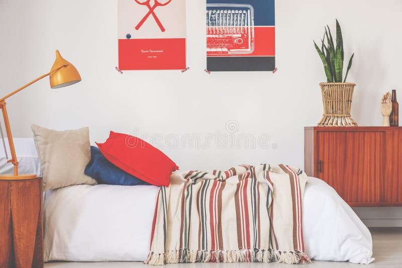 Foto real de un interior rojo y azul del dormitorio con una cama, una lámpara y carteles fotos de archivo