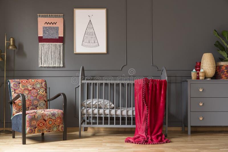 Foto real de un pesebre del bebé con una manta roja, una butaca, lámpara fotografía de archivo