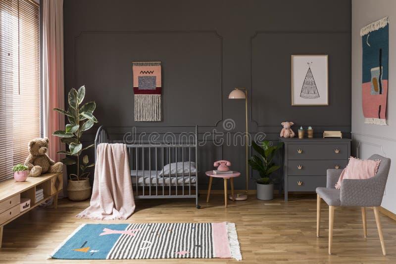 Foto real de un pesebre gris que se coloca al lado de un taburete rosado, una lámpara foto de archivo libre de regalías