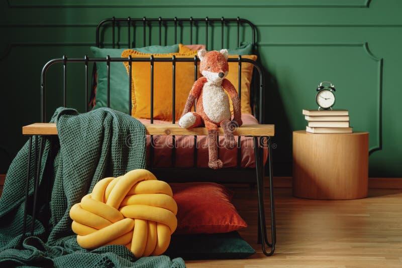 Foto real de una almohada del nudo, de una manta verde y de un zorro de la felpa en un banco de madera delante de una cama negra  fotos de archivo