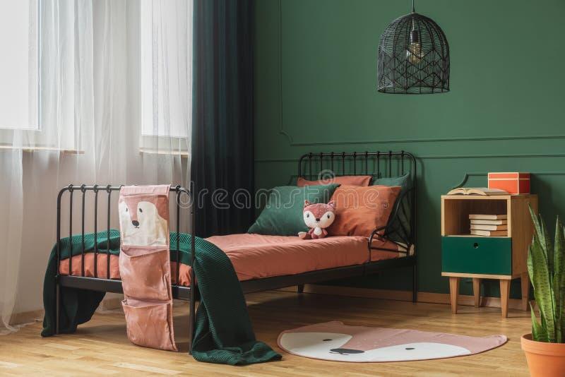 Foto real de una manta formada como un zorro en el piso de madera del interior del dormitorio de un ni?o con las hojas y las almo fotos de archivo libres de regalías