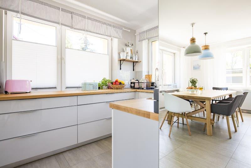 Foto real do interior brilhante da cozinha com janelas e Ta do jantar fotografia de stock royalty free
