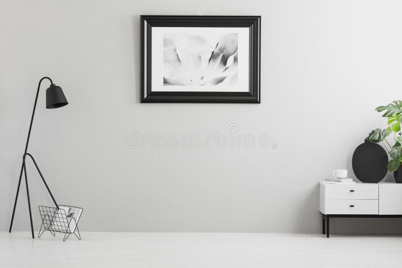 Foto real do interior cinzento brilhante da sala de visitas com cartaz simples, lâmpada do metal, o armário branco e lugar vazio  fotografia de stock royalty free