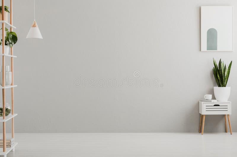 Foto reale dell'interno grigio chiaro del salone con le piante, il libro e la tazza di tè freschi sull'armadietto e sul manifesto fotografia stock