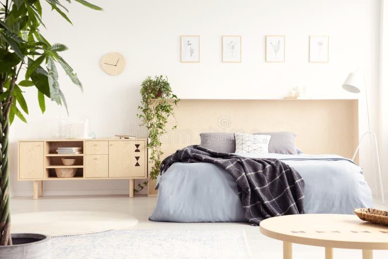 Foto reale dell'interno luminoso della camera da letto con l'armadietto di legno con immagini stock libere da diritti