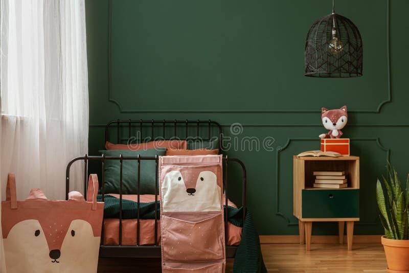 Foto reale della condizione del letto del metallo contro la parete verde scuro con il modanatura nell'interno della camera da let immagini stock libere da diritti