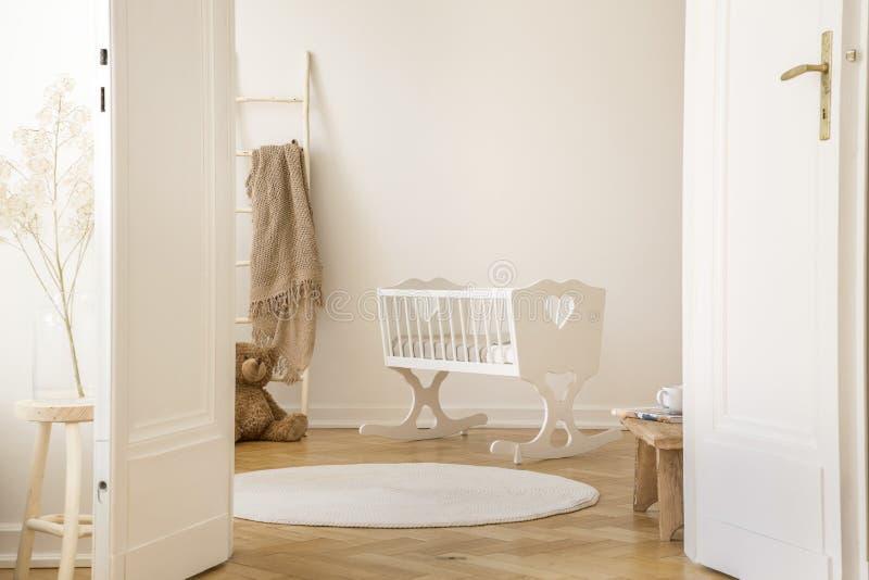 Foto reale della culla bianca con cuore che sta nell'interno della stanza del bambino di Scandi con l'orsacchiotto, il parquet di immagine stock libera da diritti