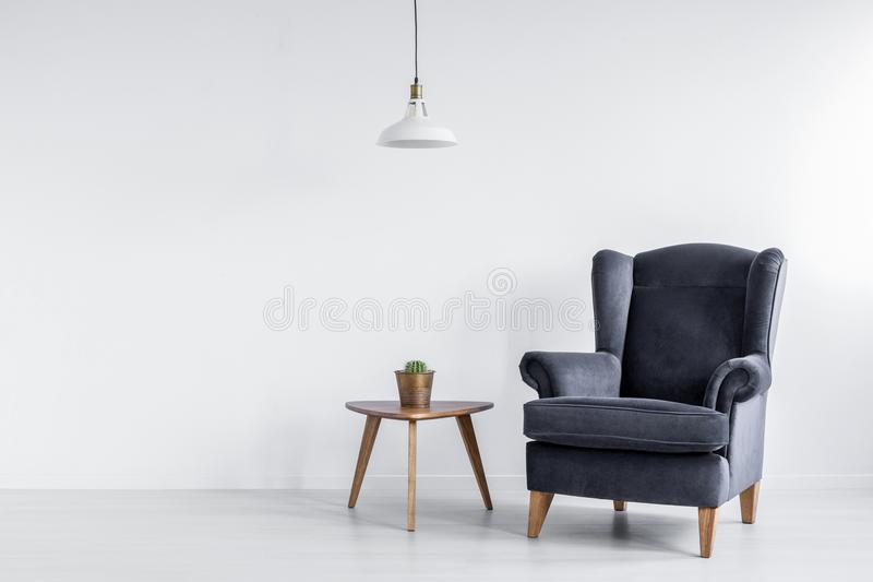 Foto reale della poltrona grigio scuro che sta accanto alla tavola di estremità di legno con il cactus nell'interno luminoso dell immagine stock libera da diritti