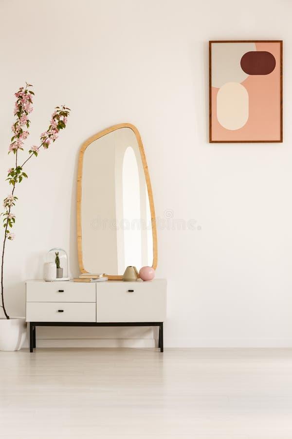 Foto reale di un armadietto con uno specchio che sta accanto ad una pianta immagine stock