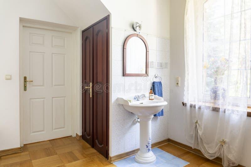 Foto reale di un interno classico della camera da letto con le porte, il lavabo, lo specchio e la finestra decorati con le tende immagine stock