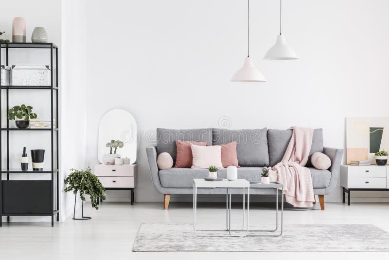 Foto reale di un interno del salone con un sofà, cuscini, tavola fotografia stock libera da diritti