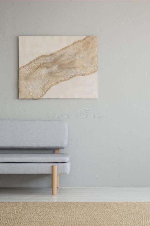 Foto reale di un interno minimo del salone con un artwo della tela da imballaggio immagine stock libera da diritti