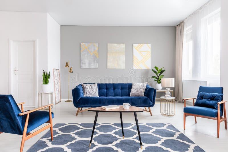 Foto reale di un interno moderno del salone con un sofà, armchai fotografie stock