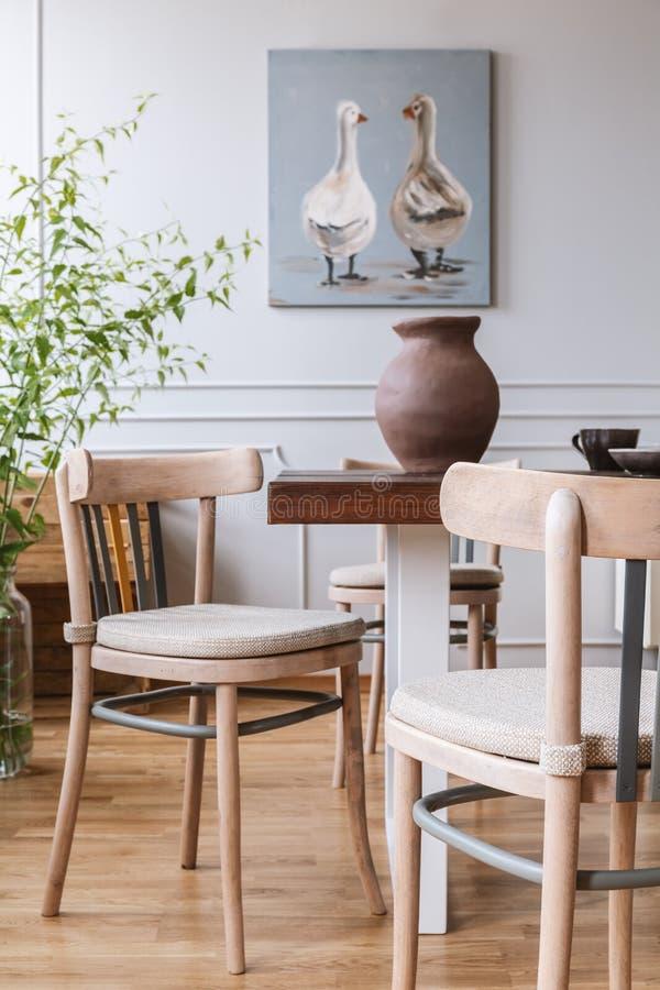 Foto reale di un interno quotidiano naturale della stanza con le sedie, la tavola, il vaso dell'argilla e la pittura con le anatr immagine stock