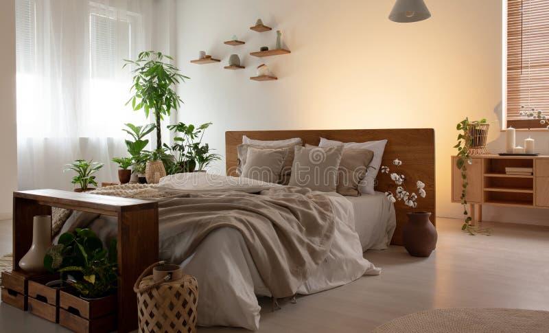 Foto reale di un interno romantico della camera da letto con un letto matrimoniale con gli strati, le piante e gli scaffali di le immagini stock libere da diritti
