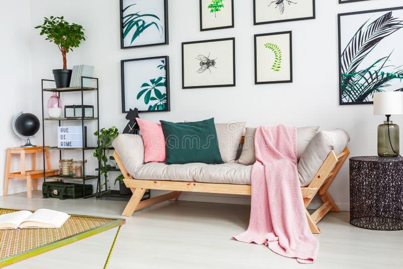 Foto reale di un sofà che sta accanto ad una parete con le pitture e fotografie stock
