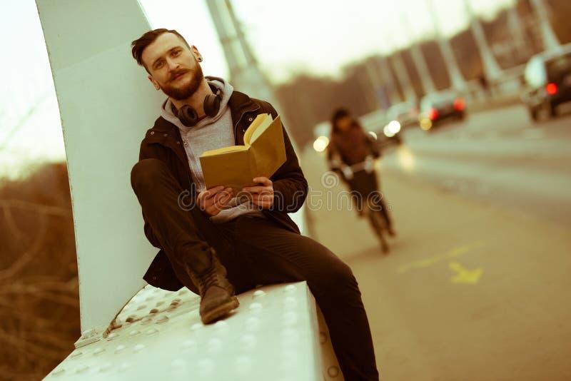 Foto retra del estilo de una lectura del hombre del inconformista en un puente imagen de archivo libre de regalías