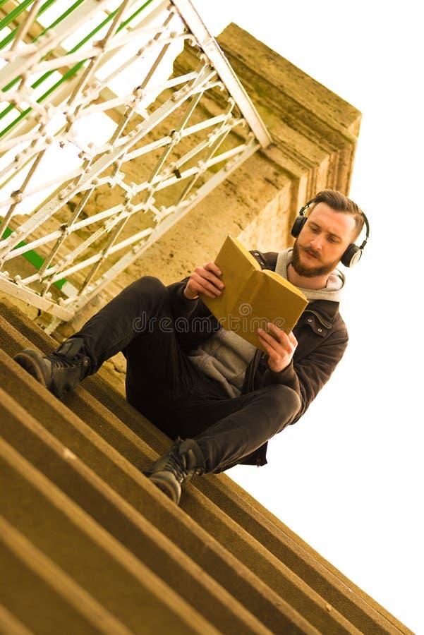 Foto retra del estilo de una sentada y de una lectura del hombre del inconformista imagenes de archivo