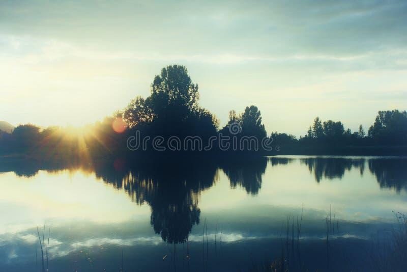 Foto retro do estilo do por do sol sobre um lago com silhuetas da árvore foto de stock