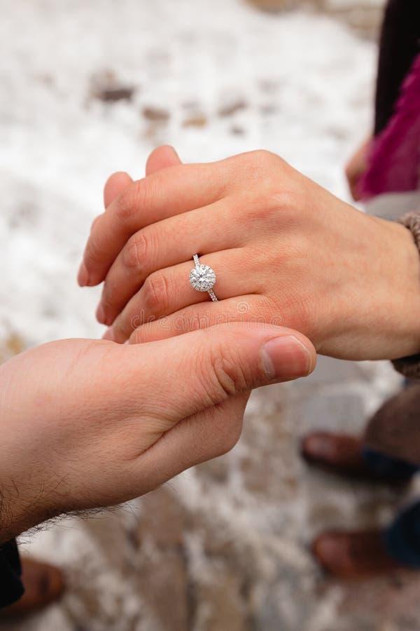 Foto romantica delle coppie sveglie all'aperto nell'inverno Giovane che propone di sposarlo con l'anello - si tengono per mano immagini stock libere da diritti