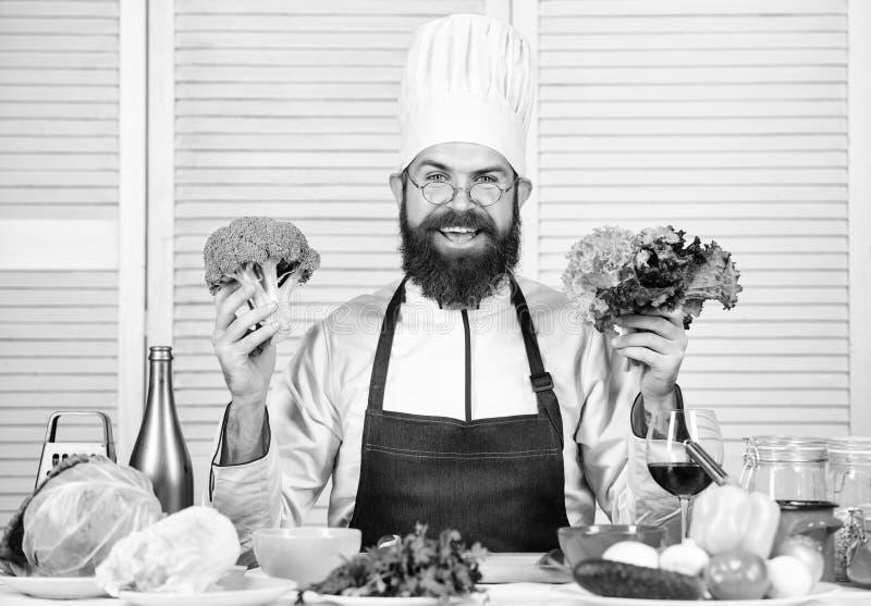 Foto's van voedsel vegetari?r Rijpe chef-kok met baard Gebaarde mensenkok in culinaire keuken, Chef-kokmens in hoed Geheime smaak royalty-vrije stock foto's