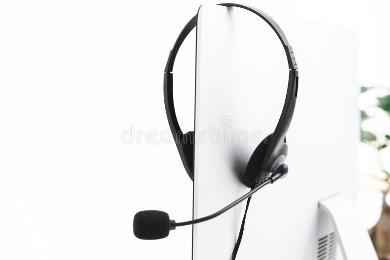 Foto-Schließung des Mikrofonkopfs für Helpline-Hilfe und Silbercomputer im Büro stockbilder