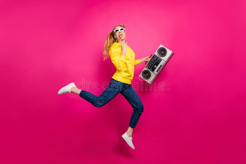 A foto sem redução da senhora fresca que salta o balancim funky alto DJ veste equipamento ocasional o fundo cor-de-rosa isolado imagens de stock