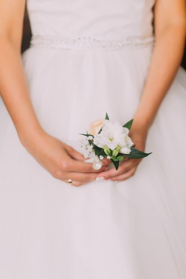 Foto sensual da moça no vestido branco que guarda o boutonniere pequeno bonito, close-up foto de stock