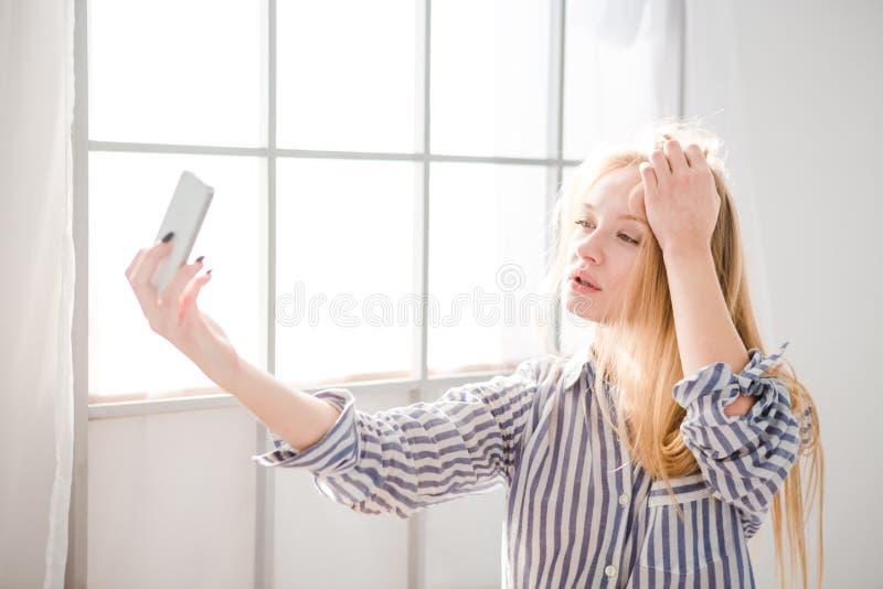 Foto sensual do takig da jovem mulher dsi mesma que usa o telefone celular fotografia de stock