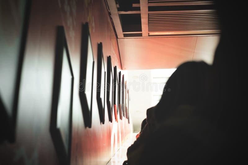 Foto Silhouette de pessoa em pé perto dos quadros fotográficos foto de stock royalty free