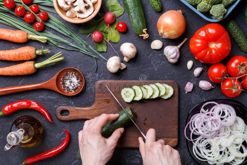 Foto sobre legumes frescos, cogumelos, placa de corte, óleo, faca, mãos do cozinheiro imagem de stock