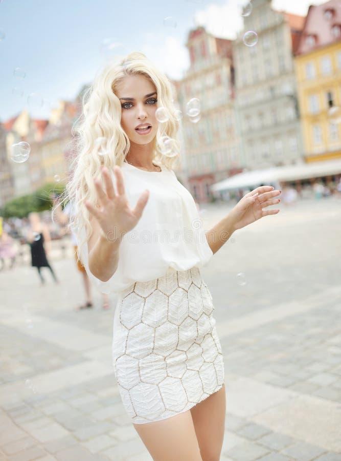 Foto som framlägger blondinen som fångar bubblor royaltyfria foton