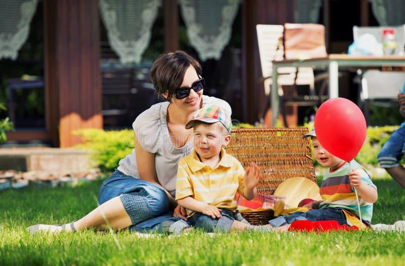 Foto som framlägger den lyckliga familjen i trädgården arkivfoton