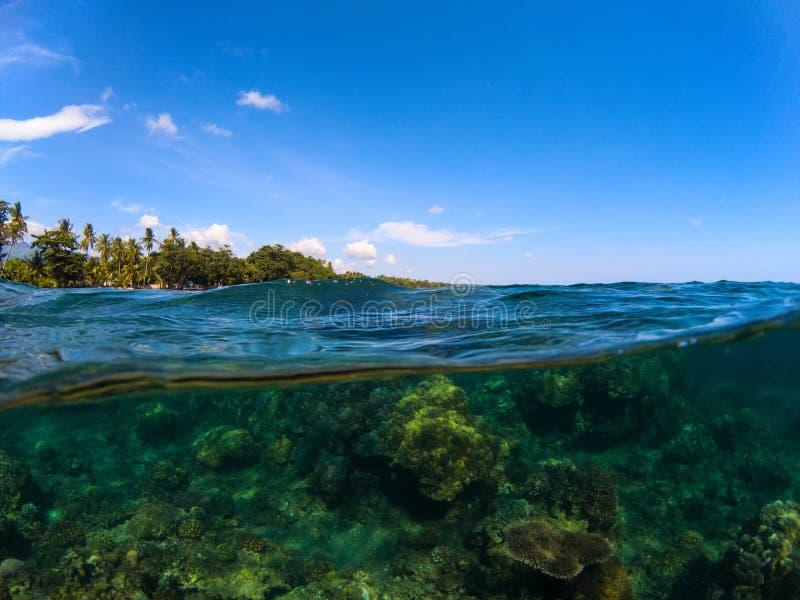 Foto spaccata con l'isola tropicale e la barriera corallina Chiaro cielo blu e vista subacquea immagine stock libera da diritti