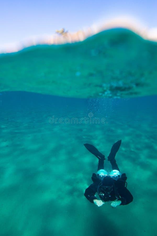 Foto spaccata di vista con nuoto maschio del subaqueo sotto l'acqua fotografia stock libera da diritti