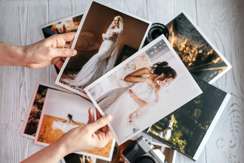 Foto stampate di nozze con la sposa e lo sposo, una macchina fotografica nera d'annata e mani della donna con due foto immagini stock