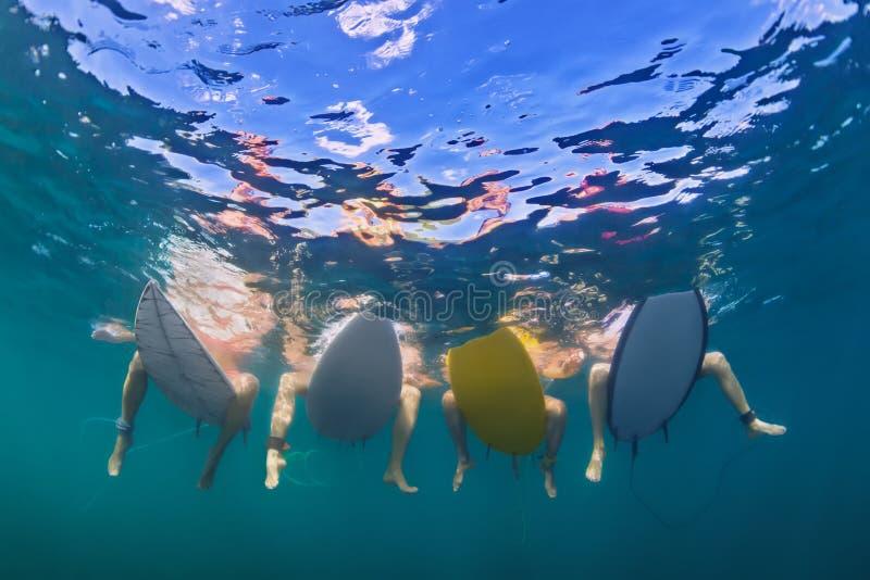 Foto subacquea dei surfisti che si siedono sui bordi di spuma immagini stock