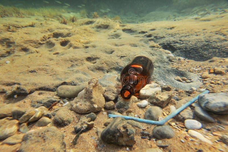 Foto subacquea - piccola bottiglia di birra marrone e paglia di plastica blu sul fondo marino Concetto di figliata dell'oceano fotografia stock