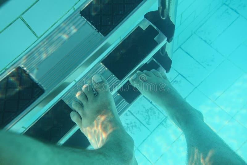 Foto subacquea, piedi dell'uomo che fanno un passo sulle scale dello stagno fotografie stock libere da diritti