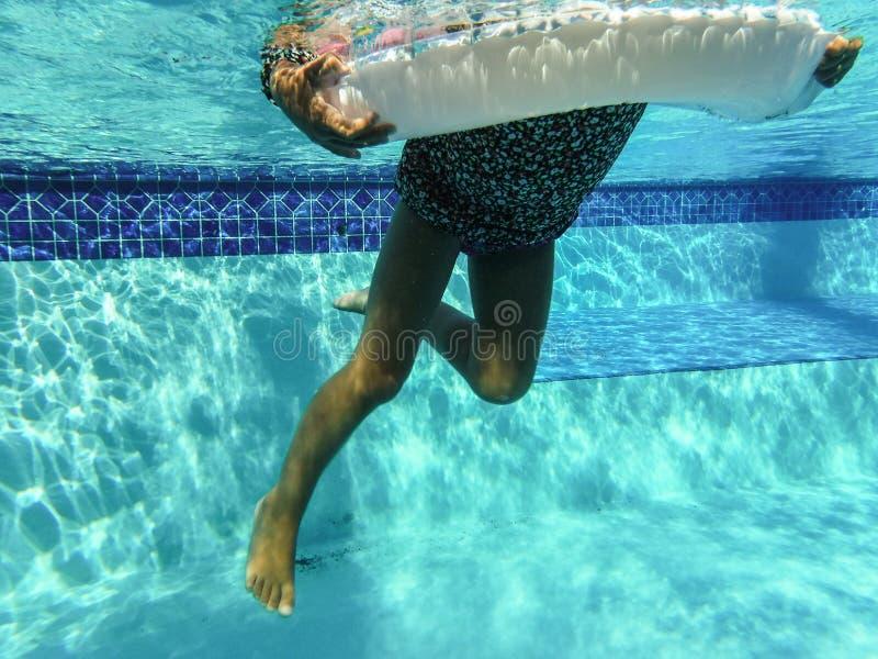foto subacuática de la natación de la muchacha en piscina con la flotación circular imágenes de archivo libres de regalías