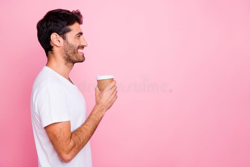 Foto sul profilo dell'uomo medio-orientale funky e positivo che tiene in mano una tazza con il caffè e ha tempo libero dopo il la immagine stock