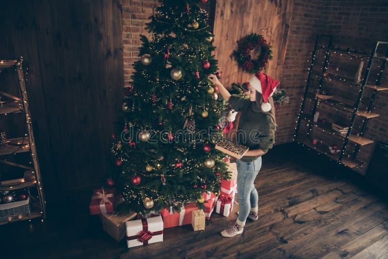 Foto superior del ángulo alto foto de brunette positiva de pelo chica bauble en árbol de abeto verde siempre preparado para Navi imagen de archivo libre de regalías