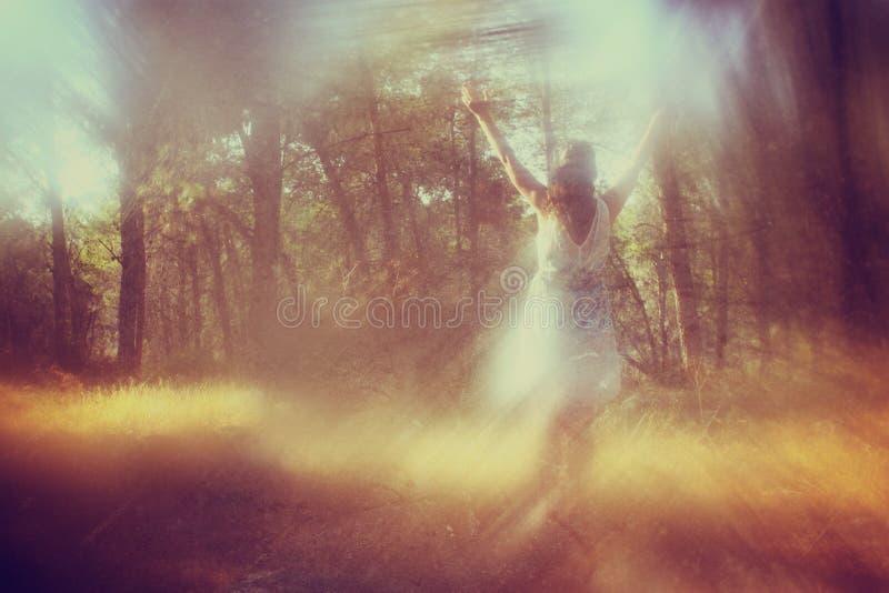Foto surreale della giovane donna che sta nella foresta i fotografie stock