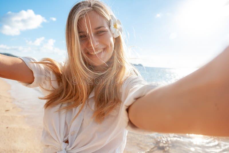 Foto teenager bionda turistica del selfie della ragazza di vacanza di viaggio con il telefono sulla festa tropicale fotografie stock libere da diritti