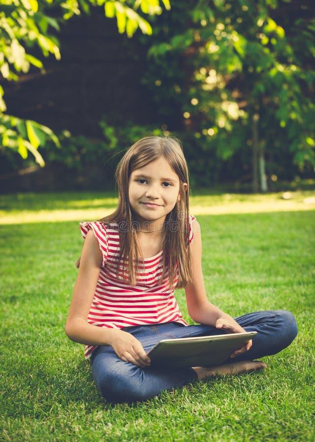 Foto tonificada da menina bonito que senta-se no gramado e que usa a tabela digital foto de stock royalty free